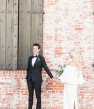 Bride approaching groom near brick wall