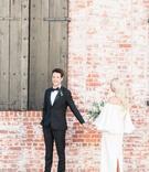 Bride approaching groom near brick wall