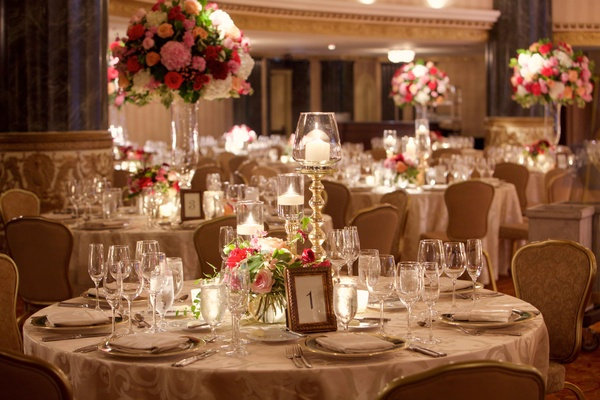 Round ballroom wedding reception table with table number in gold frame low centerpiece blush marsala