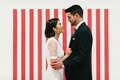 bride and groom in front of white red stripe backdrop