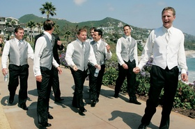Groom and groomsmen walk along beach without suit jackets