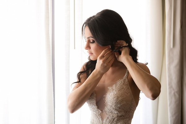 Bride in Galia Lahav sheer wedding dress putting on earrings in front of sunny window