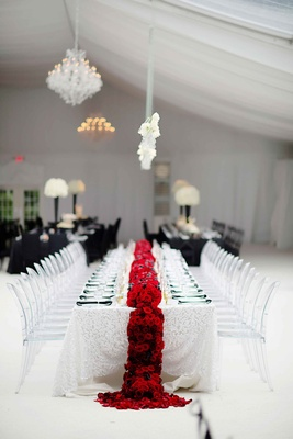 White wedding table linen with red flower runner and clear chairs