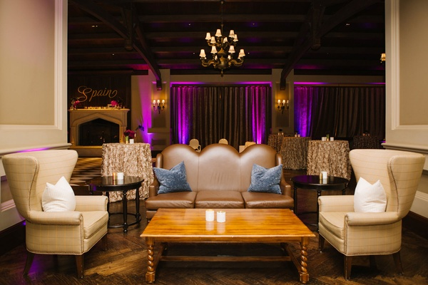 Wedding lounge area next to dance floor purple uplighting on curtains plush furniture and pillows
