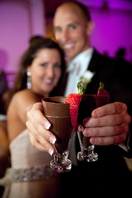 Bride and groom holding shot glass with chocolate and strawberry
