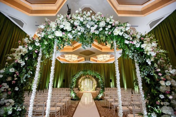 wedding ceremony indoor hotel ballroom greenery flower arches with flower cascading