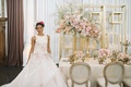 bride in floral ball gown next to taupe champagne tablescape pink centerpieces gold candelabra