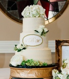 Wedding cake with monogram on center tier hydrangea on top and rose on other tiers peony flowers