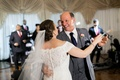 Bride in an off-the-shoulder Sottero and Midgley lace dress dances with father in grey suit