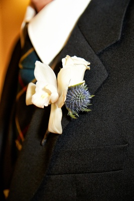 Groom's boutonniere of white orchid & rose, and blue flower on charcoal blazer lapel, tartan tie