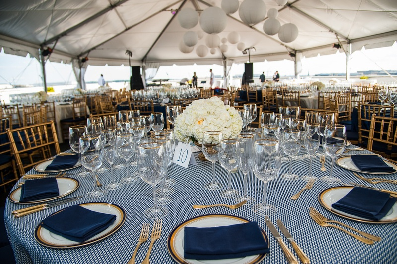 Round Tables With Gold Chairs And Blue Napkins