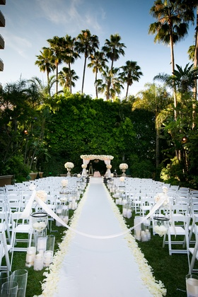 Outdoor wedding ceremony on grass lawn with white flowers