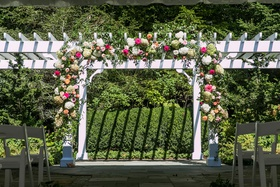 wedding ceremony arbor outdoor venue pink white orange flowers greenery