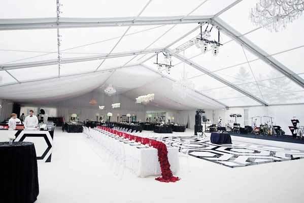 Reception tent with black and white dance floor and red flower runner