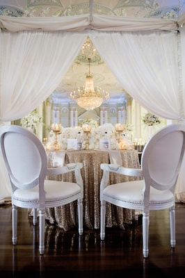 White upholstered round-back chairs at gold sweetheart table