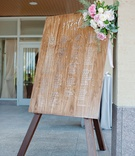 Wedding reception wood seating chart with calligraphy flowers in corner greenery peony rose blooms