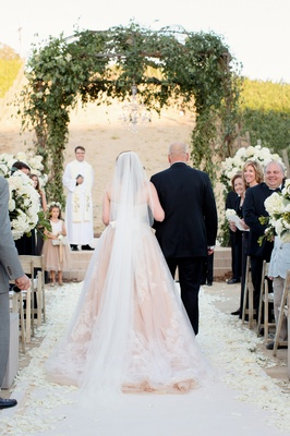 Bride in blush gown walking down aisle with father of bride