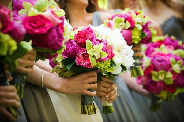 Bridesmaids' bouquets of bright pink and green flowers