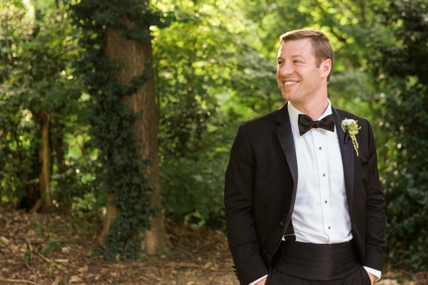groom in tuxedo with hands in pocked smiling outside