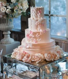 wedding cake on mirror stand sugar flowers tiers with pink butterfly designs urn with flowers