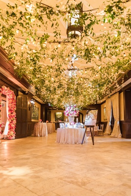 entrance to wedding reception with ceiling covered with greenery and bistro lights