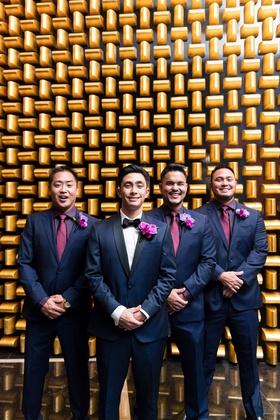 groom in navy tuxedo with black lapels, groomsmen in navy suits, purple shirts, fuchsia ties