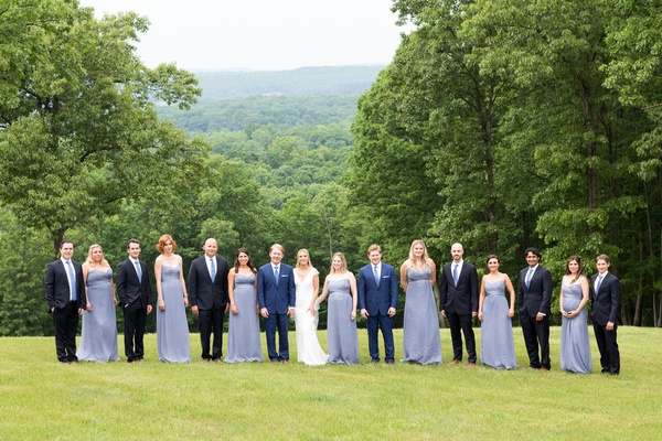 Bride and groom on family farm with bridesmaids in light blue long dresses groomsmen in suits