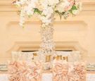 Wedding reception with pink and white flowers on quartz stand, pink chair sleeves with ruffles