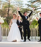 Young couple raise hands in celebration after ceremony