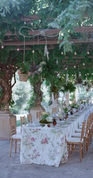 Wisteria canopy over long dinner table with flower print linens