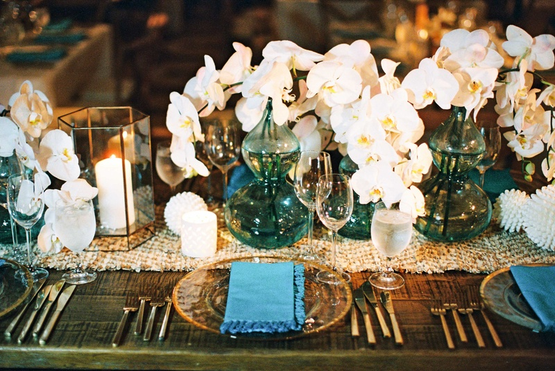Wedding reception wood table woven jute leather table runner candles, white orchids blue vases,