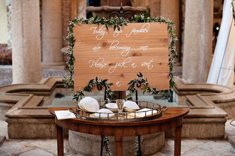 Gold tray with white yarmulkes and wood sign