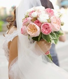 Bride in veil and lace dress holding bouquet of pink garden rose flowers and white flowers greenery