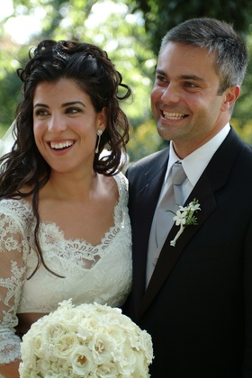 Bride in lace wedding dress and groom in black suit and grey tie