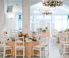 white reception space colorful tablescapes champagne colored linens round tables Ukrainian wedding
