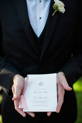 Groomsman holding ceremony program with pink calligraphy and monogram pink ribbon on side
