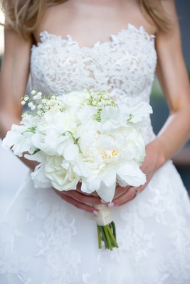 Bride with blonde hair strapless reem acra wedding dress holding white bouquet manicure