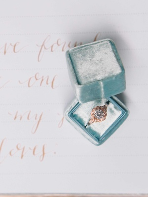 a rose gold ring inside a blue velvet The Mrs. Box on a white guest book with rose gold calligraphy