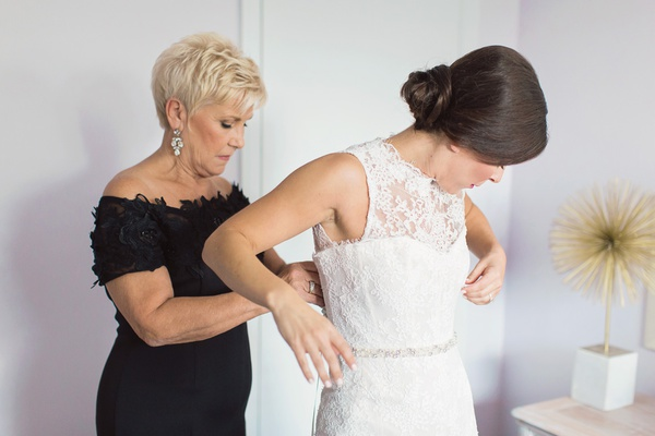 bride in monique lhuillier sleeveless mermaid wedding dress, mother of the bride in black helping