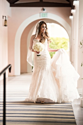 bride in kittychen couture lace gown holding train, mantilla veil