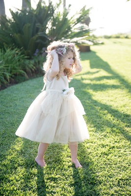 Flower girl in an off-white dress with straps, ribbon belt with large white flower, tulle skirt