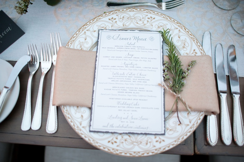 White plate with ornate design and blue menu card calligraphy greenery twine runner