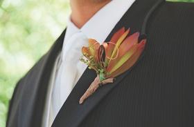 Groom wearing orange flowers on lapel