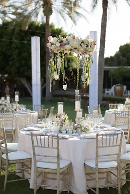 Garden wedding reception with floral chandeliers, tables in white tablecloths and weathered chairs