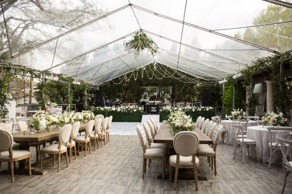 wedding reception under clear top tent wood floor greenery hedge wall neutral decor