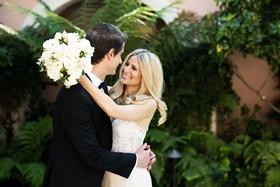 bride in inbal dror wedding dress holding white wedding bouquet hugging groom in tuxedo bel-air