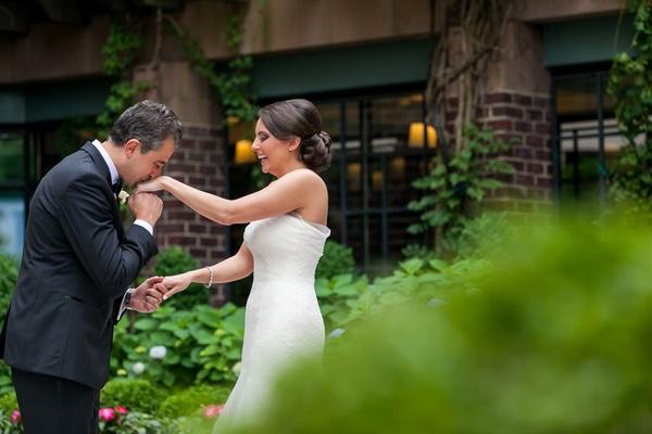 groom kisses brides hand first look wedding washington dc four seasons tuxedo dress