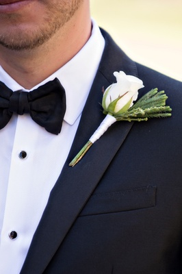 Groom in tuxedo with white rose boutonniere wrapped with ribbon