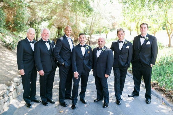 Groom and groomsmen with family and officiant in tuxedos with bow ties