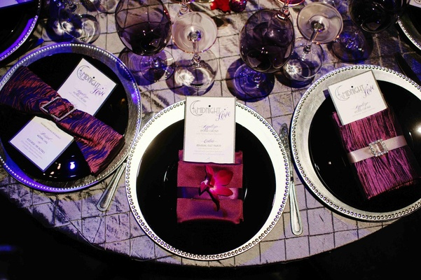 Black plates on silver chargers with purple napkins